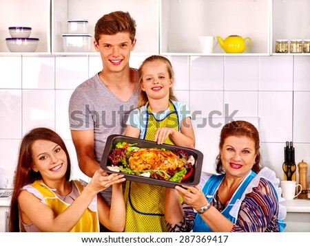 Happy family with grandmother at kitchen. Cooking roast chicken.
