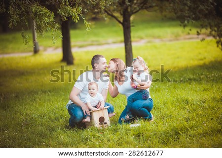 Happy family with nesting box and colorful paints in green summer forest