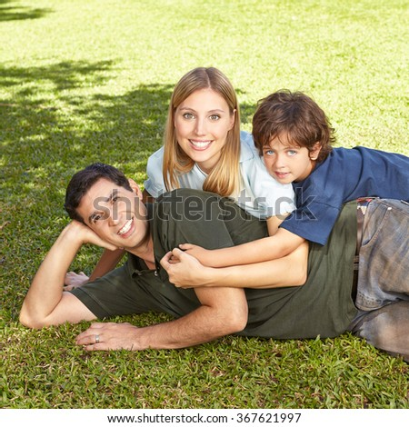 Happy family with son laying in summer in grass of a garden