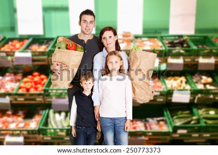 Happy Family With Two Children Holding Groceries Bag Full Of Vegetables
