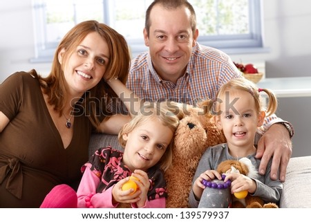 Happy family with two daughters and pregnant mother at home.