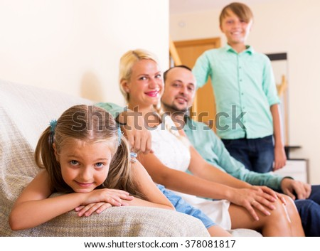 Happy family with two little kids on couch indoors. Focus on the girl
