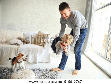 happy father playing with his baby daughter in the bright living room near the window . The concept of friendly family.