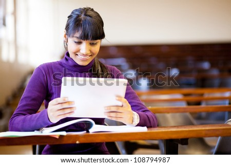 happy female indian college student using tablet computer in classroom