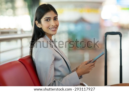 happy female passenger at airport using tablet computer while waiting for her flight