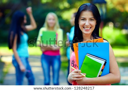 happy female student with colorful books outdoors
