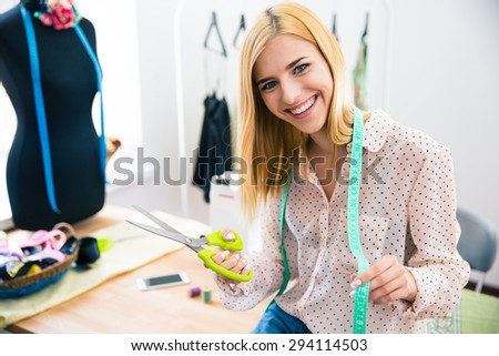 Happy female tailor standing in workshop
