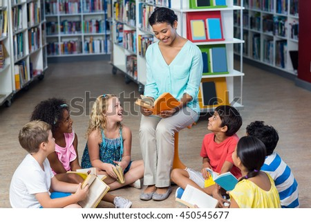 Happy female teacher with students reading books in library