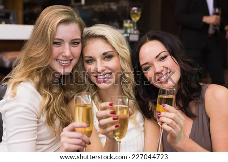 Happy friends drinking champagne together at the bar