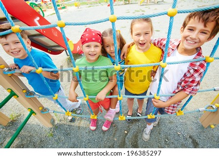 Happy friends looking at camera on playground outdoors
