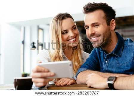 Happy friends looking at smartphone at cafe
