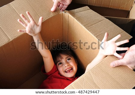 Happy girl (age 6-7) hide inside a big cardboard box moving into a new house. Moving home concept. Real people. copy space