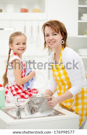 Happy girl and mother washing dishes together wearing aprons