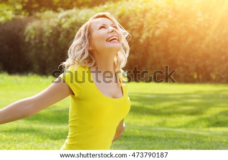Happy girl enjoying the Nature on green grass. Beautiful blonde young woman smiling. Outdoor