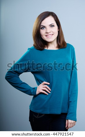 happy girl in a blue shirt holds hand on your belt and smiling on a gray background