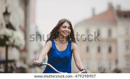 Happy girl is riding a bike on the street