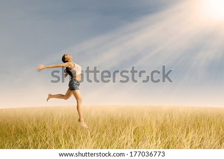 Happy girl jumping at golden wheat  in summer