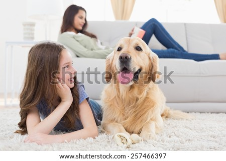 Happy girl looking at dog while lying on rug at home