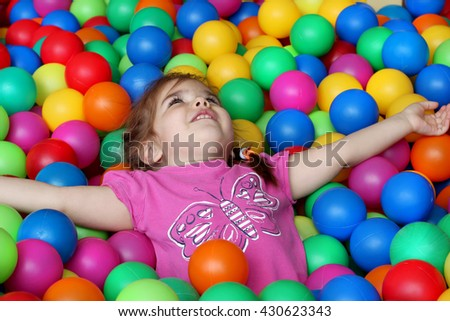 Happy girl playing and having fun at kindergarten with colorful balls, family weekend concept, happy birthday and merry party