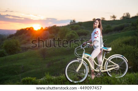 Happy girl with retro bike standing at hill and looks to the camera, with a blurred background of greenery and beautiful sunset