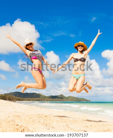 Happy girls jumping on the beach. Summer concept.