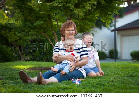 Happy grandmother with two little boys celebrating July 4th