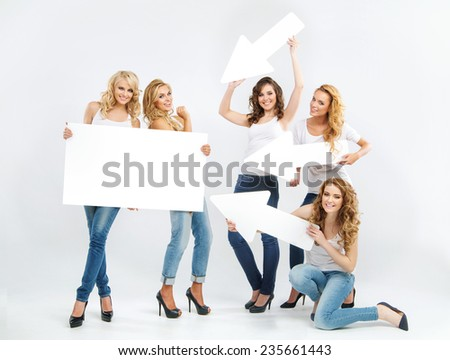 Happy group of female friends with empty board