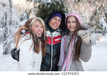 Happy group of young people in the snow-covered trees