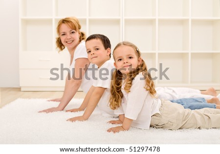 Happy healthy family making gymnastic exercises together - focus on the little girl