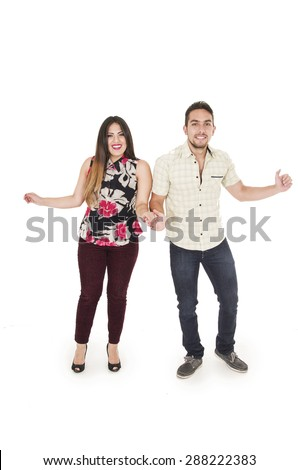 happy hispanic couple dancing next to ech other with one arm each to the side