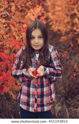 happy kid girl eating berries on cozy warm autumn walk, outdoor activities