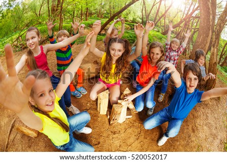 Happy kids raising their hands up in the forest
