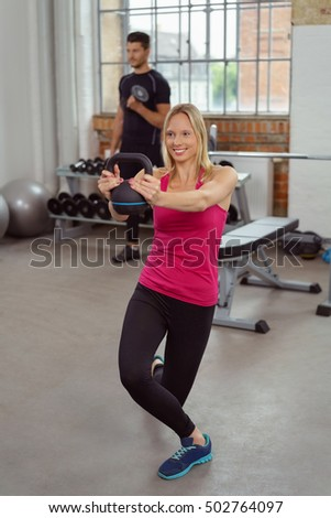 Happy lady in pink doing kettle bell workout at indoor fitness gym with man behind her using weights