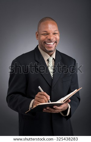 Happy laughing businessman with notepad in his hands