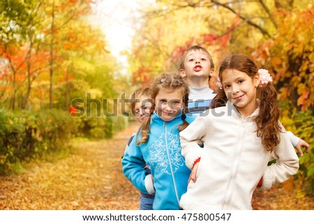 Happy laughing kids playing in an autumn park