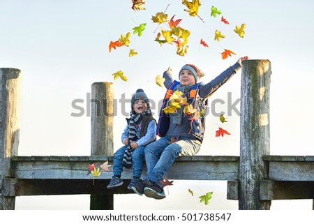 happy laughing kids throwing autumn fall leaves, sitting on a boardwalk at lake