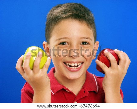 Happy little boy holding and eating fresh apples on blue background.