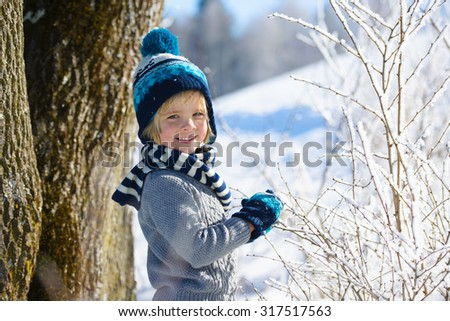 Happy little  boy in winter hat in snow forest