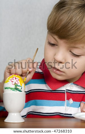 Happy little boy painting the easter eggs
