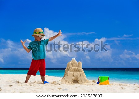 happy little boy with built sandcastle on tropical beach