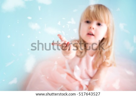 Happy little girl catching snowflakes in her hands on blue background. Winter time.