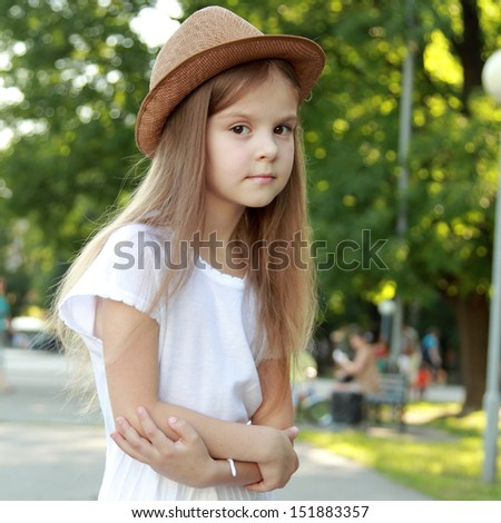 Happy little girl in a beautiful hat outdoors