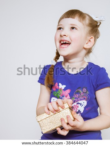 Happy little girl opening a gift box
