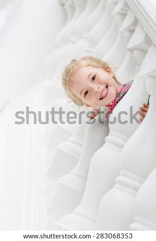 Happy little girl playing on a white background