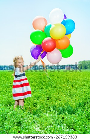 Happy little girl with a bunch of colorful balloons on a summer meadow.