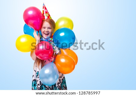 happy little girl with balloons on blue background