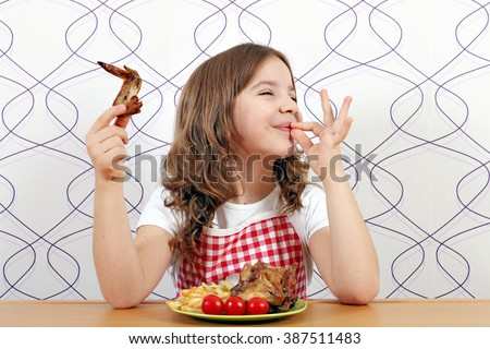 happy little girl with chicken wings and ok hand sign