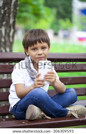 Happy Little smiling child boy hand holding mobile phone or smartphone making selfie portrait photoon a background of summer park