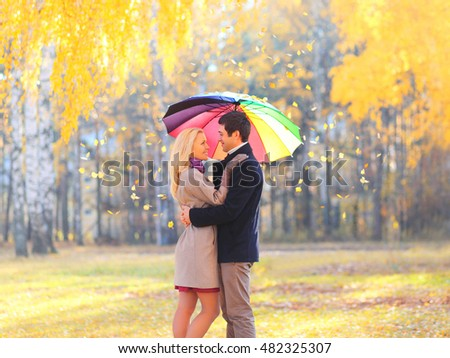 Happy loving couple with colorful umbrella in warm sunny day over yellow flying leafs background
