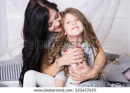 Happy loving family. Mother and daughter  playing and hugging on a bed